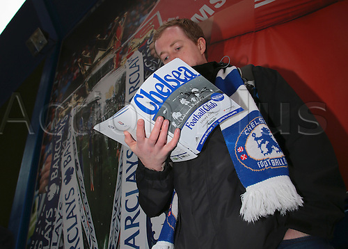 05.03.2016. Stamford Bridge, London, England. Barclays Premier League. Chelsea versus Stoke City. A Chelsea fan reads the Match Day Program as he waits for the Stamford Bridge turn stiles to open