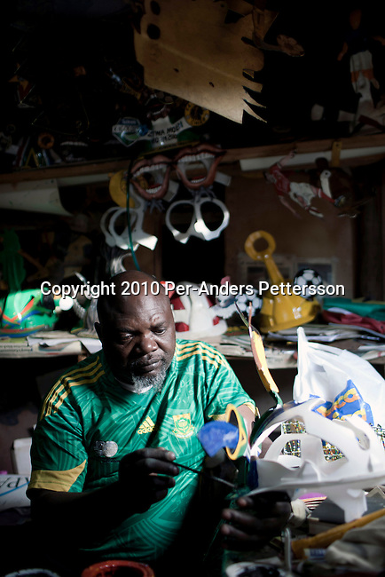 JOHANNESBURG, SOUTH AFRICA - MAY 10: Alfred Baloyi, an artist, and the founder of the Makarapa Helmet, works inside his old studio in a squatter camp in Primrose, Johannesburg, South Africa. Mr. Baloyi, and a diehard Kaizer Chiefs soccer fan, started to make these hats in 1979. Initially he asked a friend who worked at a construction site for a helmet, as he wanted to protect himself from missiles at games. He later started to paint it, and later started to make this different figures hand cut out from the helmet. During the years he has made many different artistic hats that are on display in his studio in a shack in Primrose, Johannesburg. He later gave up his job as a washer of busses. From his small workshop in a squatter camp in Primrose south east of Johannesburg he recently made partner with an investor and have a brand new factory with about fifty people employed to make the hats. (Photo by Per-Anders Pettersson/Getty Images)