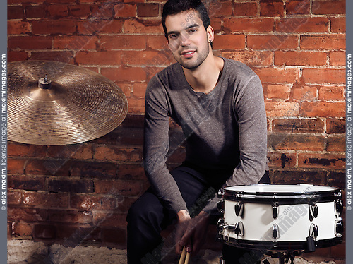 Young man musician with drums sitting at a brick wall artistic portrait