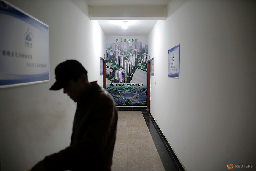 A migrant worker passes time at the offices of a subcontractor company at the construction site of Zixia Garden development complex in Qianan, Tangshan City, Hebei province, China January 28, 2016.  REUTERS/Damir Sagolj