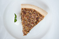 a Slice of Pecan Pie on a plate with whipped cream and mint