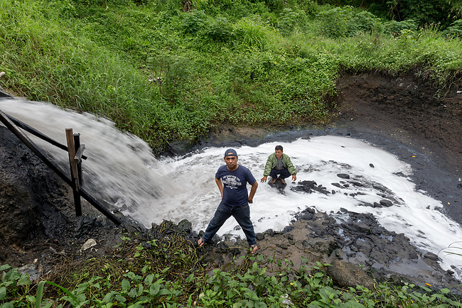 29 JAN, 2018, Bandung, Indonesia:  Anti pollution activists Asep Hasbi (blue shirt) and Kasim Karsono at an industrial sewer outlet dumping waste from toxic dye factories into the Cihaur tributary at Batujajar village down from Saguling dam. The tributary feeds the Citarum river, listed as one of the most polluted rivers in the world.  It will soon be the main water supply system for Jakarta as the bores that have been dug into the aquifers dry but it also supports agriculture, fishery, industry, sewerage and electricity.  The Indonesian Government is moving to urgently try to clean the system up but it is fighting massive infrastructure issues and toxic industrial dumping.    Picture by Graham Crouch/The Australian
