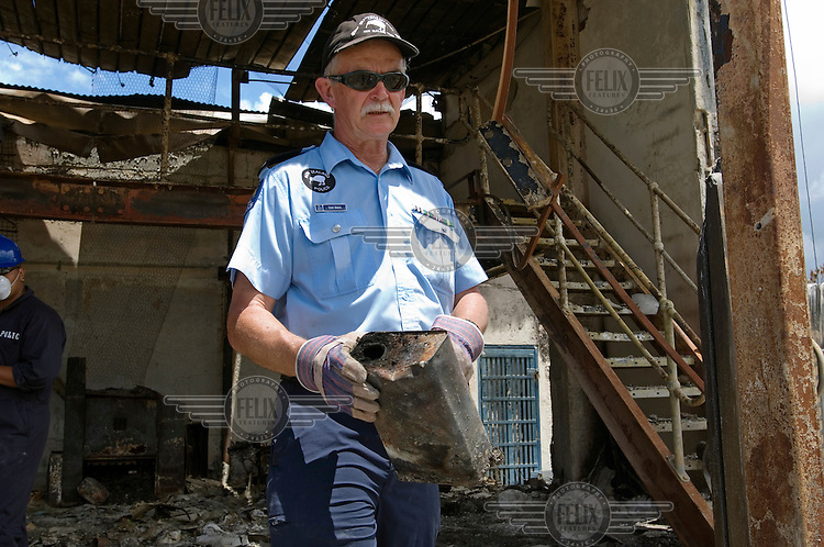 Tony White, a Royal New Zealand Police officer, holds a petrol can found after the NZ police force assisted the Tongan police force with forensic investigations following the Nuku'alofa riots on Thursday 16th November 2006. This building, a photo processing lab and shop, was the seat of one fire, which quickly burnt out the whole block when fanned by winds. The disturbance began after the government stalled on legislation setting up a more democratic election in 2008 as it closed for the year.