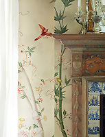The fireplace in the sitting room has a blue and white Delft tile surround; the wallpaper, a faded botanical print, has been bleached by years of bright sun.