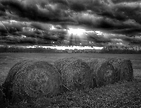 Storm clouds move across the harvested soybean field and rolls of hay at the Braun Farm in Westerville OH