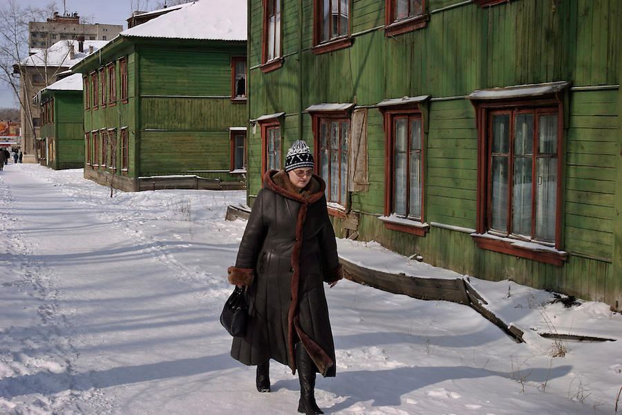 Khabarovsk, Russia, 01/03/2004.&amp;#xD;A woman walks past dilapidated old  private houses in the city centre.&amp;#xD;<br />