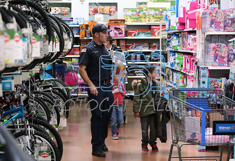 Shoppers browse at the 10th annual Holiday with a Hero event at Walmart in Carson City, Nev., on Wednesday, Dec. 17, 2014. The event pairs 200 of Carson City's K-5th grade homeless students with a local heroes for Christmas shopping. <br />