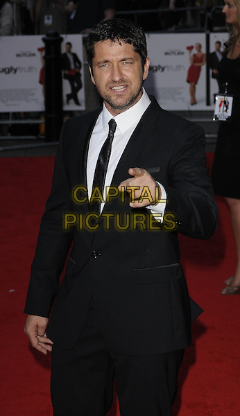 "GERARD BUTLER.The UK film premiere of ""The Ugly Truth""  held at the Vue West End, Leicester Square, London, England..August 4th 2009.half length black suit jacket tie white shirt  funny face suit hand arm stubble facial hair .CAP/CAN.©Can Nguyen/Capital Pictures."