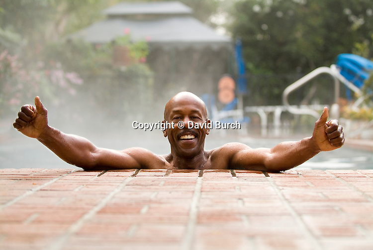 Man with arms out in swimming pool, smiling