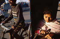 View inside an auto rickshaw with a woman looking into her bag while a bicycle overtakes,