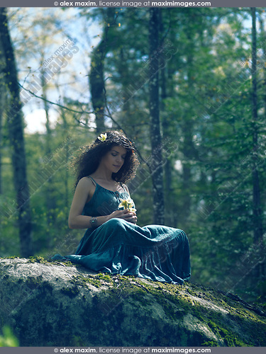 Artistic tranquil portrait of a beautiful young woman in a green dress and with a wreath on her head sitting in the nature contemplating a wild flower in her hands
