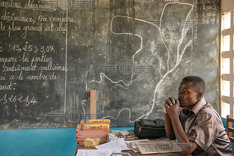 A teacher sits at his desk beside a blackboard on which is drawn a map of Congo.
