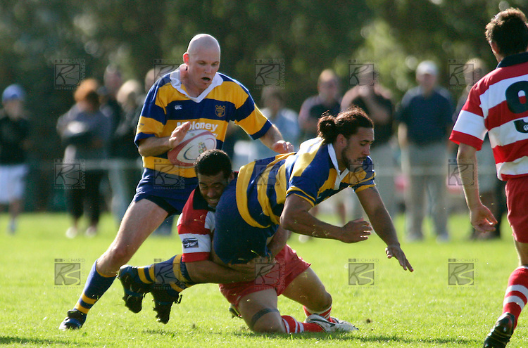 A. Poa manages to get the pass away to P. Wheeler as he is taken to ground by T. Tuifua Counties Manukau Premier Club Rugby, Patumahoe vs Karaka played at Patumahoe on Saturday 22nd April 2006. Karaka won 19 - 6.