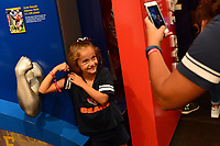 Canton, OH - August 4, 2018: At the Pro Football Hall of Fame Museum in Canton, OH, a child poses for her mother beside a trubute to the size and strength of Seatle Seahawks lineman Cortez Kennedy, August 4, 2018. (Photo by Don Baxter/Media Images International)