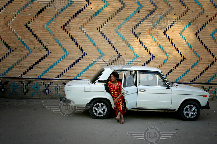 A woman sits in the rear of a Lada car parked near the Registan.