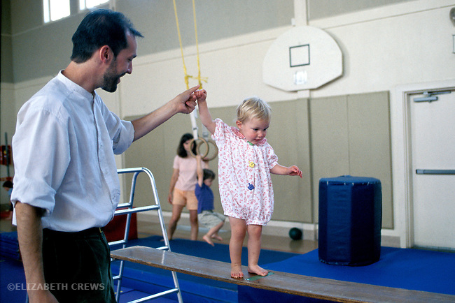 Albany, Ca Father helping daughter two years old learn to balance on plank at gymnastics program for preschool children