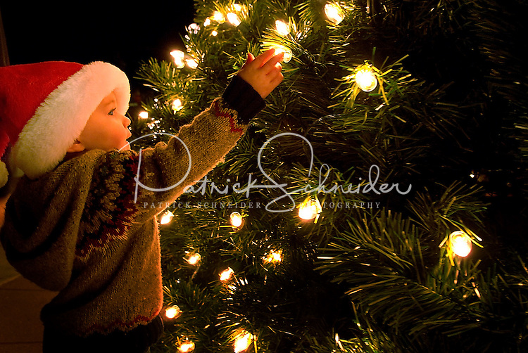 A young child reaches to touch the Christmas tree lights during the annual Christmas tree lighting event at Birkdale Village in Huntersville, NC. Birkdale Village combines the best of shopping, dining, apartments and entertainment venues within a 52-acre mixed-use development.
