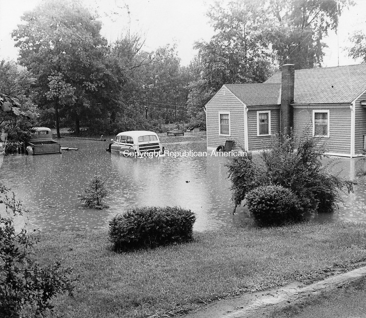 Some Residents were caught unaware when flood waters in July 1963 flashed down brooks and streams, stranding vehicles such as the car and pickup at the Howard Magnuson home at 126 Westbury Park Road.
