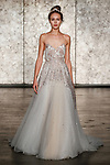 Model walks runway in a spaghettie strap sequined soft golden tulle ballerina ballgown, from Inbal Dror Fall 2018 bridal collection on October 5, 2017; during New York Bridal Fashion Week.