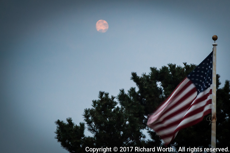 The gibbous moon behind a thin, smokey veil of  clouds over the U. S. Flag at the San Leandro Marina on San Francisco Bay.