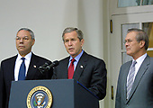 """United States President George W. Bush announces his intention to withdraw the US from the 1972 ABM Treaty with the Russian Federation in the Rose Garden of the White House in Washington, DC on December 13, 2001. He called it a """"Cold War relic"""".  Left to right: US Secretary of State Colin Powell; President Bush; and US Secretary of Defense Donald Rumsfeld.<br /> Credit: Ron Sachs / CNP"""