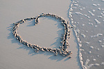 A heart drawn in the sand with the tide coming in to one side