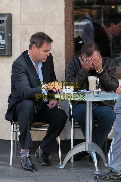 Peter Jones & Duncan Bannatyne spotted in London, England..July 28th, 2011.full length jeans denim brown leather jacket black shirt suit blue sitting cafe drink coffee beverage looking down  hands covering face sad upset dragons' den.CAP/HIL.©John Hillcoat/Capital Pictures .