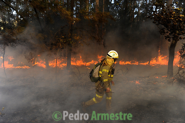 Members of the Galician fire brigade works around the fire area in Porqueira, on August 14, 2010, near A Coruña. (c) Pedro ARMESTRE