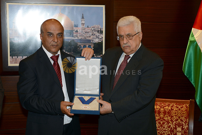 Palestinian President Mahmoud Abbas (Abu Mazen) gives the artist Jamal Saeed Badwan, Medal of Merit and Excellence Gold in the West Bak city of Ramallah, on June 23, 2013. Photo by Thaer Ganaim