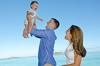 Mother and father delight in see their happy son fly through the blue sky near Kailua beach, Oahu
