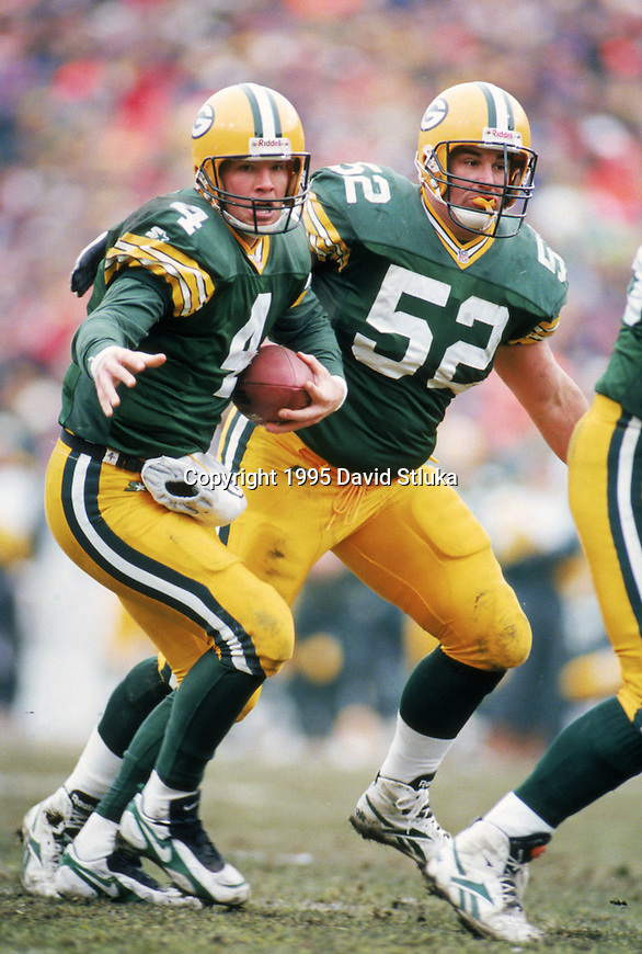 Green Bay Packers quarterback Brett Favre (4) scrambles as center Frank Winters (52) looks on during an NFL football game against the Pittsburgh Steelers at Lambeau Field on December 24,1995 in Green Bay, Wisconsin. The Packers won 24-19. (Photo by David Stluka)