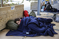 Pictured: A young family of migrants rest at the port Friday 26 February 2016<br /> Re: Hundreds of refugees that crossed the border from Turkey to the Greek islands, have arrived at the port of Piraeus near Athens, Greece