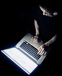 Overhead view of a young woman sitting with Apple Macbook laptop in front of her in darkness