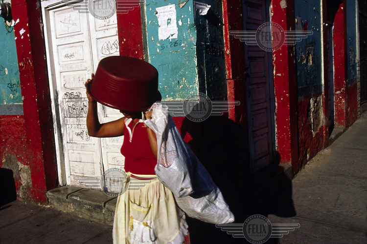 A woman uses a bowl to shield her eyes from the sun as she walks down a street in Tegucigalpa, Honduras.