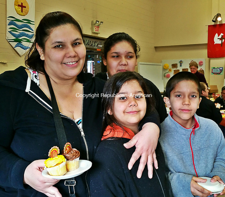 WATERBURY -- Nov. 27, 2015 -- 26_NEW_112715MDP02 -- From left, Yadira Cavan and her children, Ashen Morales, 8, Destiny Morales, 12, and Karel Morales, enjoyed the Thanksgiving feast hosted by Greater Waterbury Interfaith Ministries Thursday.