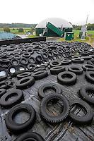 GERMANY Biogas plant and maize substratum storage with old tyres at cow milk farm / DEUTSCHLAND Nawaro Biogasanlage von PlanET Biogastechnik auf dem Hof von Landwirt Norbert Hack in Wentorf, aus dem Gas wird mit einem BHKW Strom erzeugt und ins Netz eingespeist, die Waerme wird fuer Heizung der Wohnhaeuser im Dorf verwendet, Mais Silage Substrat Lagerplatz mit abgedeckter Folie und Altreifen
