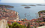 Hilltop view of the Croatian Island town of Hvar, its harbor, and outlying islands.