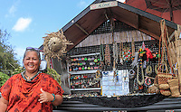 A vendor smiles and gives the shaka sign next to her custom souvenir display, which is mounted on a truck parked at the Ho'okipa Beach overlook (cliff above the beach), Maui.