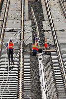 "02/26/07:  Construction workers thread wires during construction of Charlotte, NC's, new LYNX light rail lines, which opened on November 24th, 2007. More than 800 workers helped build the 9.6 mile LYNX Blue Line. The LYNX Blue Line offers fast, quiet, convenient light-rail service to 15 stations between uptown Charlotte and I-485 at South Blvd. Dozens of bus routes are timed to connect with trains at the Blue Line stations, making it easy to get to work, to shopping or wherever you need to be...NOTES FROM WIKIPEDIA: On November 24th, 2007, the first light rail line?a 9.6-mile (15.5-km) line known as the Lynx Blue Line? opened. It runs between Uptown Charlotte and stop short of Pineville, using a railroad right-of-way paralleling South Boulevard in its entirety. The line has 15 stations, it shares trackage with the Charlotte Trolley from the Atherton Mill station to the 7th Street station...Subsequently expected to open is a light rail line to the northeast. It will open in phases, with the first phase to reach 36th Street in 2013 and the second phase to reach I-485, at the University of North Carolina at Charlotte, in 2018. The corridor will be 14 miles (22.4 km) long, with 14 stations...On February 22, 2006, the Charlotte Area Transit System announced that its rapid rail lines will be called the ""Lynx."" (Lynx system map). The name fits in with the city?s cat theme (NFL team is Carolina Panthers; NBA team is Charlotte Bobcats, as well ""Lynx"" was mainly chosen because the light rail is about ""connectivity.""..The rapid rail cars will be black, silver and blue. Gold will appear around the ""Lynx"" logo to tie in the history of the Charlotte region being home to the first major U.S. Gold Rush...A commuter rail line is also planned. It will go from Uptown to the northern suburbs of Huntersville, Cornelius, Davidson, and Mooresville...Modern streetcars are also planned, with a circulator route around uptown as well as routes radiating out of downtown..... February 26, 2007."