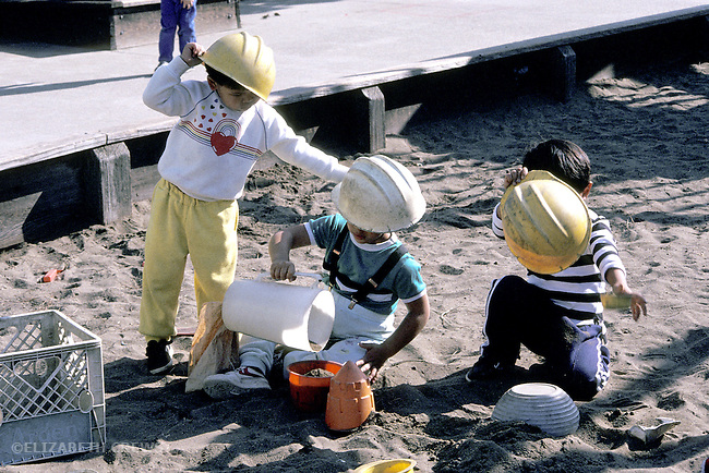 Albany CA Boys in preschool, age three and four years, playing masculine fantasy game using hard hats