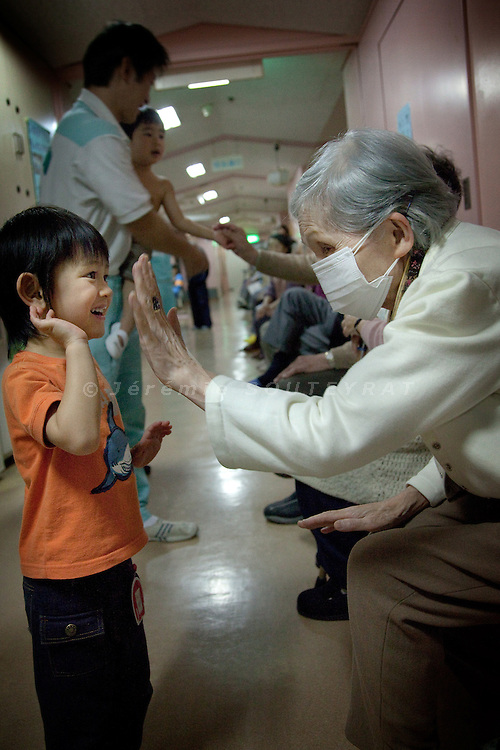 Tokyo - 3rd of December 2009 - Kotohen nursery and nursing home in the Edogawa district. An old japanese woman and a child clap their hands after the visit of the kids.