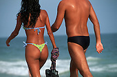 Rio de Janeiro, Brazil. Couple walking along the seafront promenade on Copacabana beach.