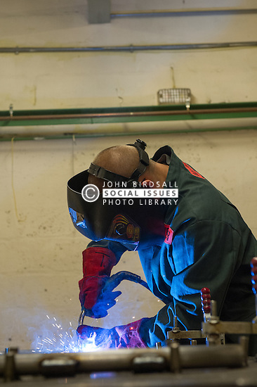 A prisoner welding in a prison workshop making prison beds in HMP Featherstone
