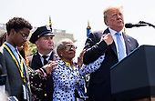 President Donald Trump holds the hand of Adrianna Valoy as he speaks about her daughter, New York Police Detective Miosotis Familia, who was killed in the line of duty, as he delivers remarks at the 37th Annual National Peace Officers' Memorial Service at the U.S. Capitol Building on May 15, 2018 in Washington, D.C. <br /> Credit: Kevin Dietsch / Pool via CNP