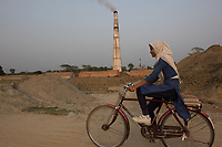 Bangladesh, Jhenaidah. Bangladesh, Jhenaidah. Muslim girl on bike passing by chimney at brick factory.