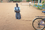 Forced to kneel in the dust, a student is disciplined at the John Paul II School in Wau, South Sudan.