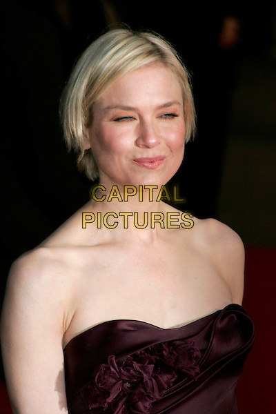 "RENEE ZELLWEGER .The ""Leatherheads"" European Film Premiere held at the Odeon cinema, Leicester Square London, England..April 8th, 2008.headshot portrait strapless purple aubergine plum blinking funny face .CAP/AH.©Adam Houghton/Capital Pictures."