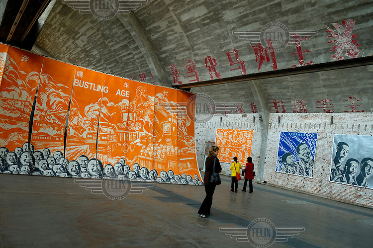 Paintings are displayed in the cavernous interior of a converted art gallery in Dashanzi, Beijing's art district. The gallery was once a factory and an old propaganda slogan  still remains painted on the walls.