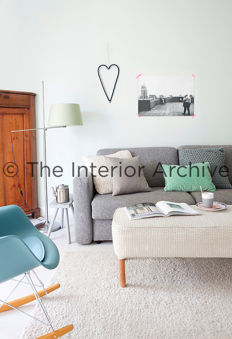 The same shade of 'Pale Powder Green' has been extended from the kitchen into the living room to create unity throughout the downstairs space