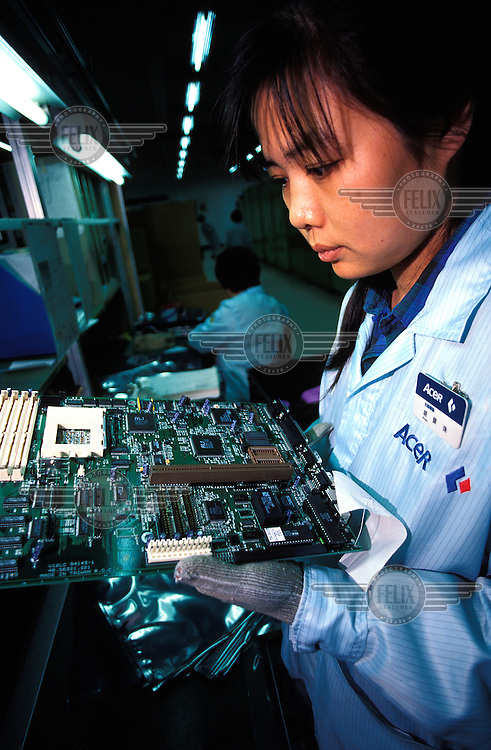 ©Chris Stowers/Panos Pictures..Worker checks PCB off the production line at an ACER computer factory in Hsin Chu, Taiwan.